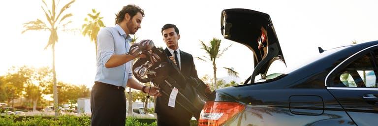 man putting golf clubs in car trunk