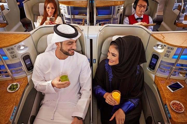 Um homem e uma mulher Emirati desfrutam de um sumo na Classe Executiva da Emirates num A380