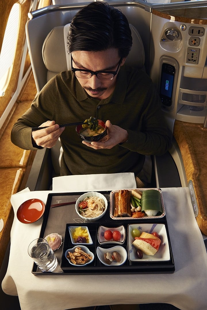 A Japanese man enjoying a bento box in Emirates Business Class on board an A380