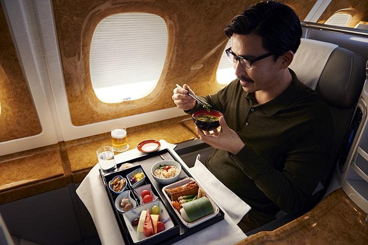 Um homem asiático desfruta de uma caixa de bento servida na Classe Executiva da Emirates