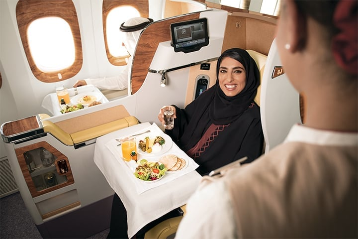 A cabin crew is helping a customer with her meal in Emirates Business Class