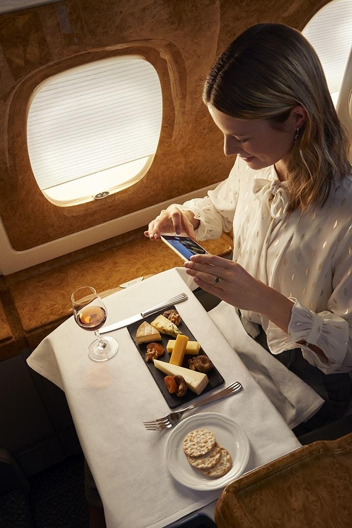 Uma mulher tira uma fotografia da sua tábua de queijos na Classe Executiva da Emirates