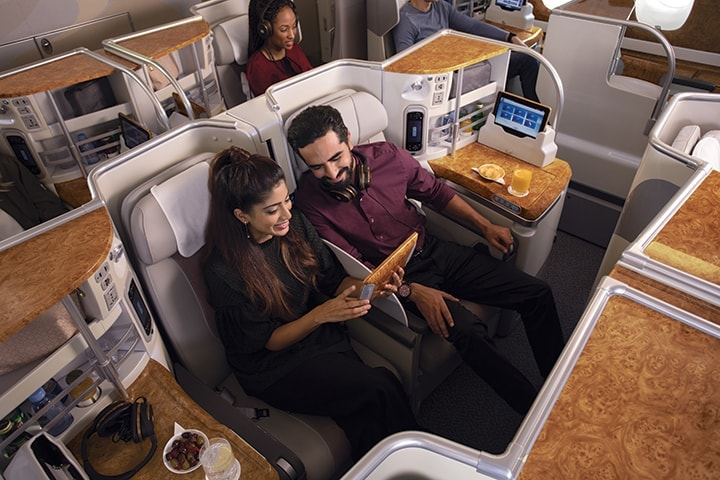 A couple browsing the inflight entertainment on their touchpad and choosing what to watch while sitting in Emirates Business Class