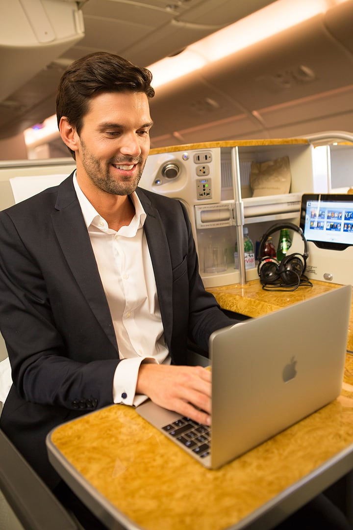 A man finishes some work on his laptop in Emirates Business Class on the Airbus 380
