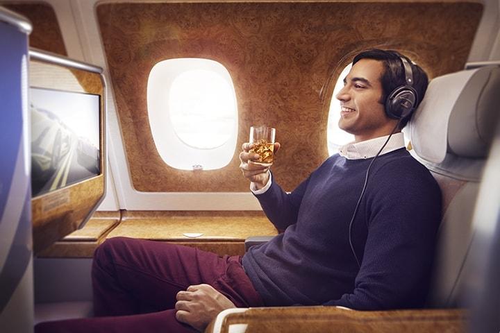 Um homem no seu lugar na Classe Executiva da Emirates olha para a TV de ecrã panorâmico e usa os auscultadores de Classe Executiva enquanto saboreia uma bebida