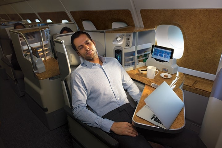 A man has fallen asleep while doing work in Emirates Business Class