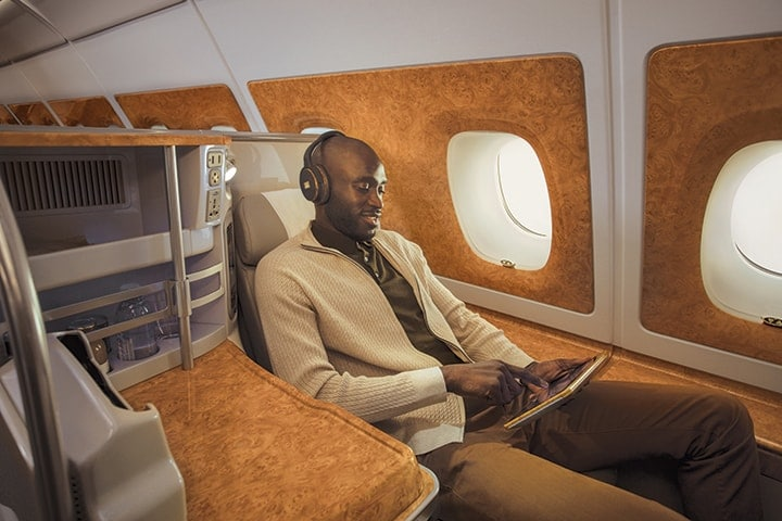 A man in his seat in Emirates Business Class browsing what to watch on the Emirates inflight entertainment system, ice via the touchpad screen