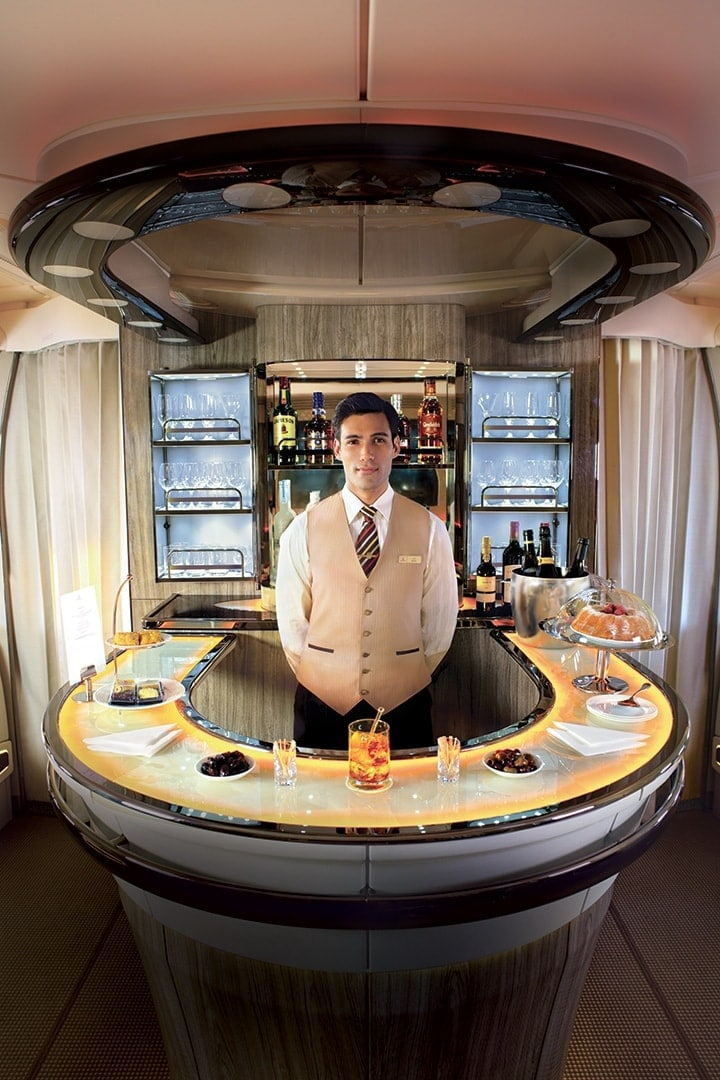 An Emirates cabin crew stands behind the bar of the Emirates A380 Onboard Lounge