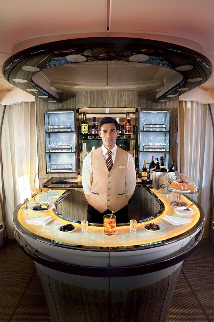 Um tripulante de cabina da Emirates está em frente ao bar no Lounge a Bordo Emirates A380