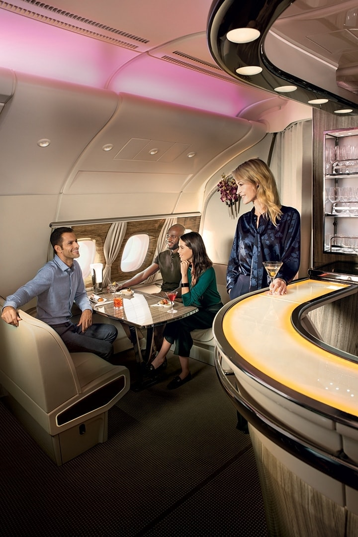 A woman looks on from the bar as a group of people socialize in the Emirates A380 Onboard Lounge