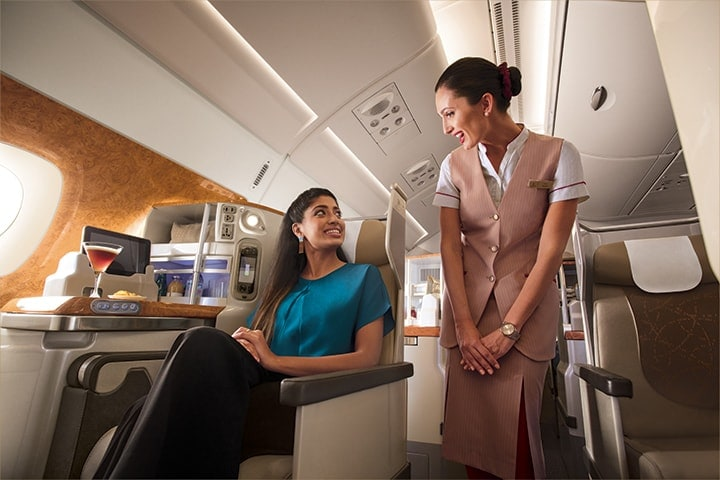 A woman asks an Emirates cabin crew for something in Business Class on an Emirates A380