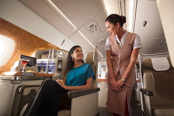 Uma mulher pede algo à tripulação de cabina da Emirates, na Classe Executiva de um Emirates A380