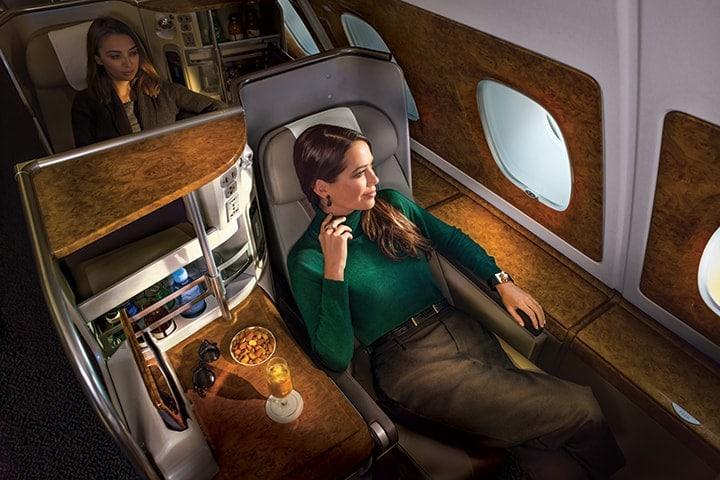 Uma mulher descontrai na Classe Executiva da Emirates, olhando pela janela e desfrutando de um copo de champanhe