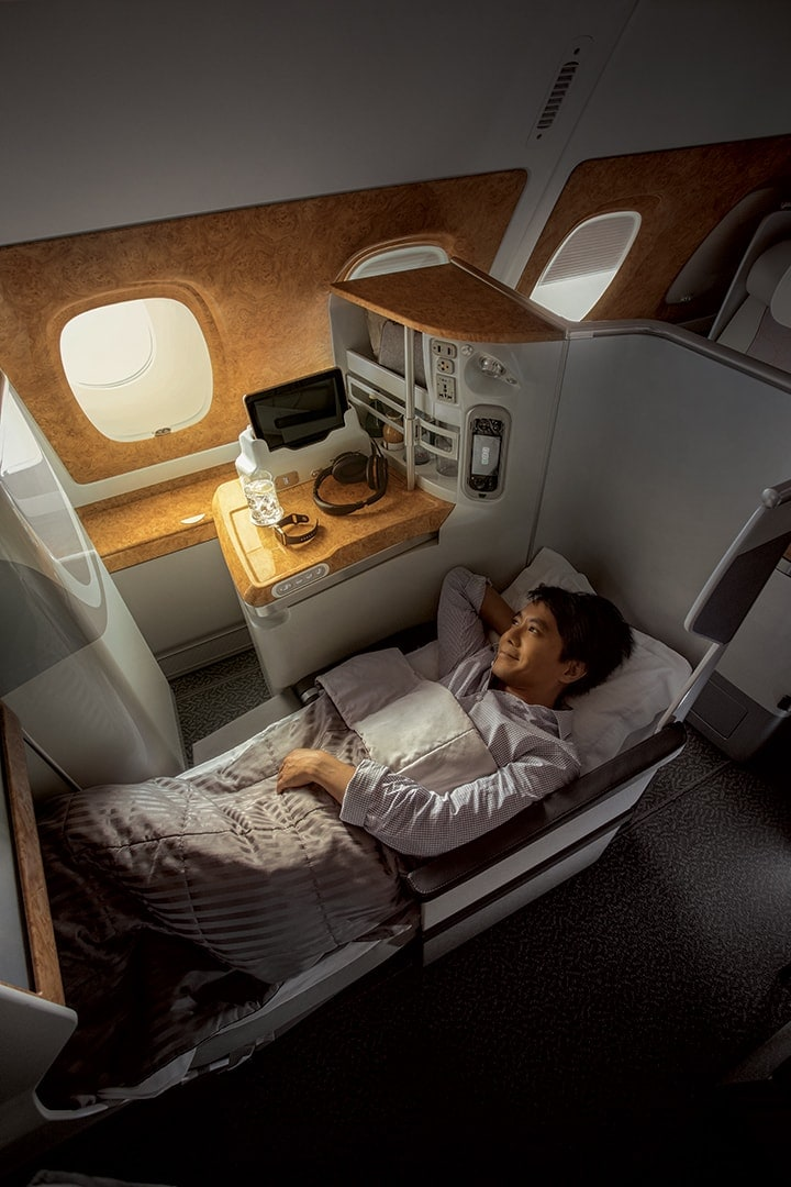 A man is stretched out in bed in Emirates Business Class with his arms above his head on the pillow on an Airbus 380