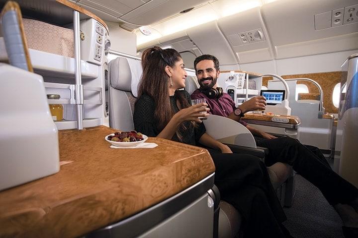 Um casal conversa enquanto toma uma bebida nos seus lugares na Classe Executiva da Emirates num Airbus A380