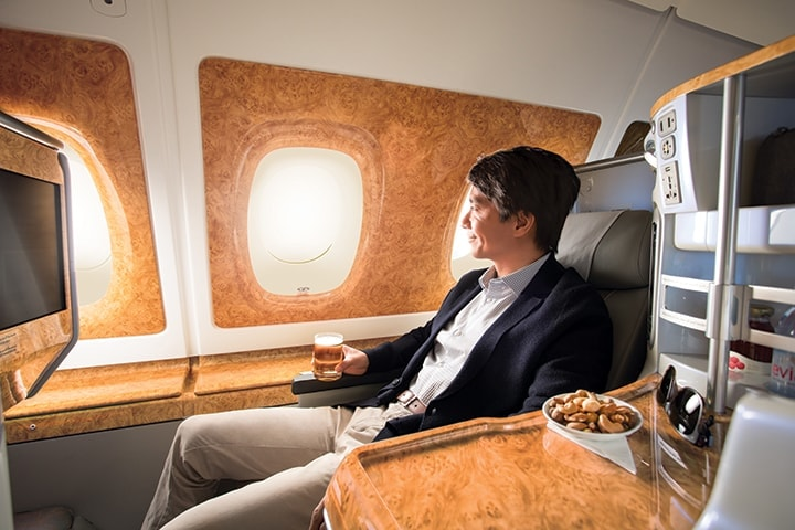 A man gazes out of his window while enjoying a glass of whiskey in Emirates Business Class