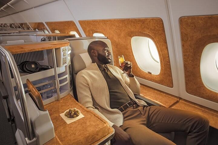 Bir adam, Emirates Business Class koltuğunda geniş ekran televizyonuna bakıyor ve içkisinin tadını çıkarıyor