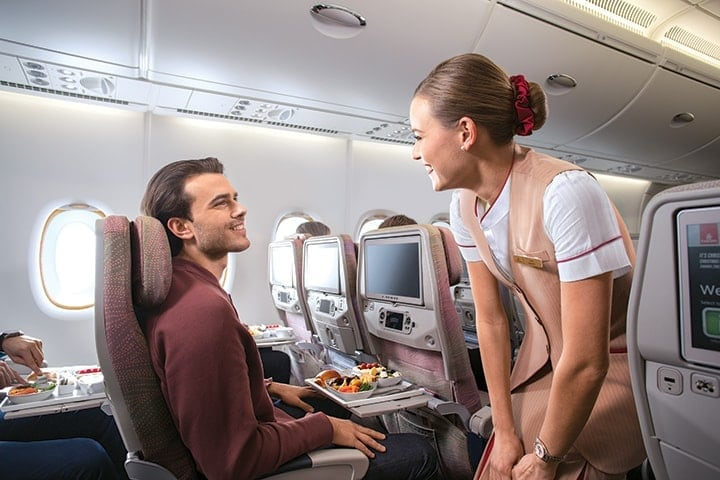 Smiling cabin crew asks a male passenger if he needs anything