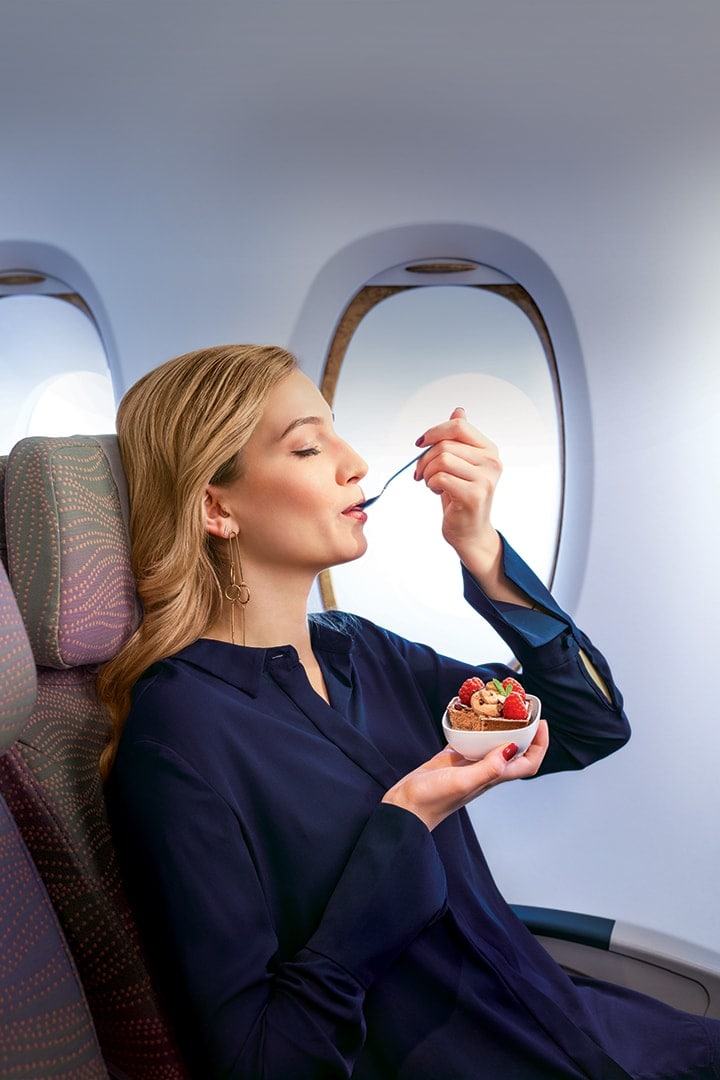 Woman eating a spoonful of dessert in Emirates Economy Class on an Emirates A380