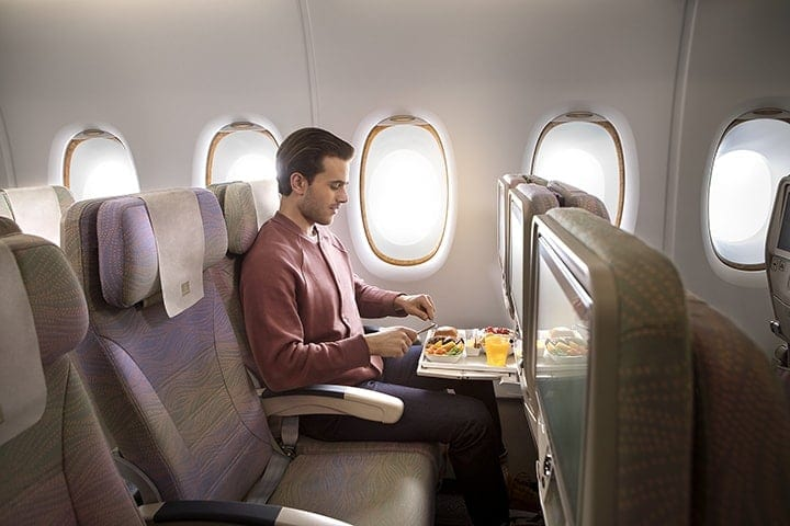 A man enjoying an inflight meal in Emirates Economy Class on an Airbus A380