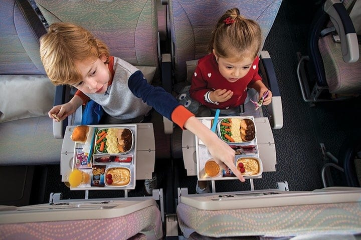 Two children enjoying their kids' meals in Emirates Economy Class on board an A380
