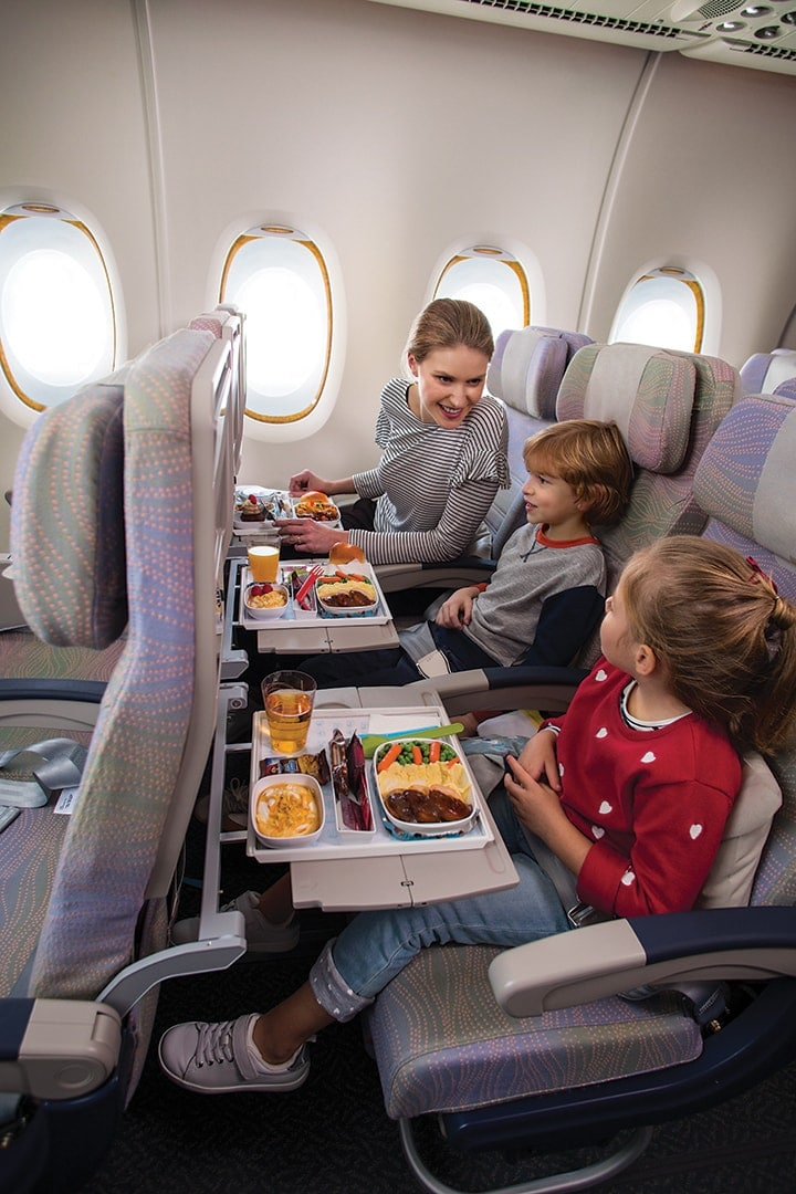 A woman and two children look at the kids' meal in Economy Class on board an Emirates A380