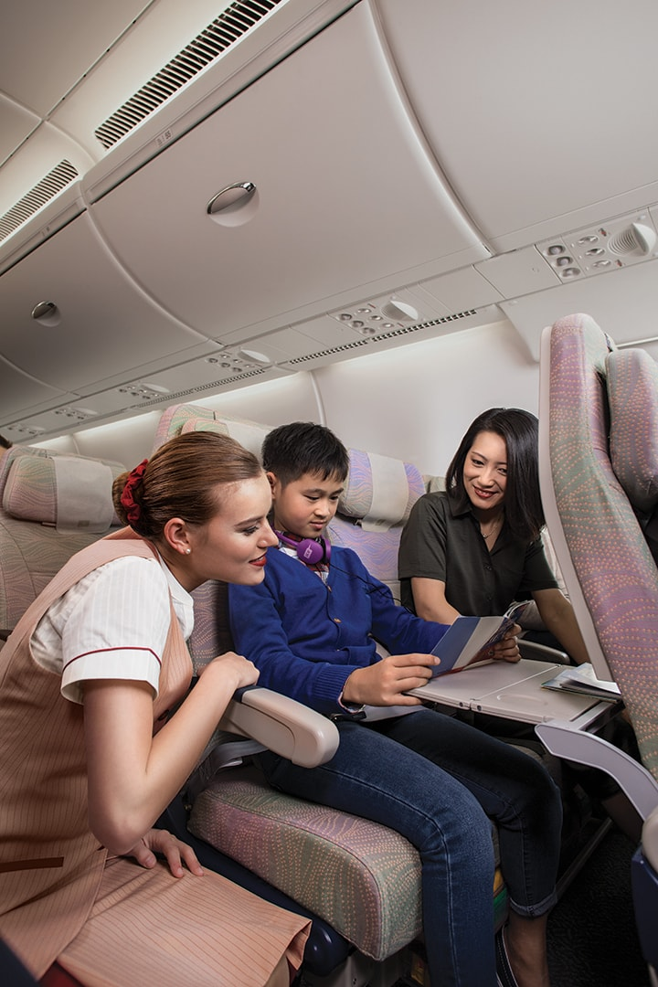 A woman helps a kid in economy class with an activity