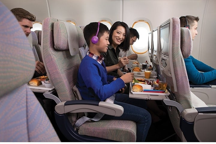 A young boy watching Emirates ice inflight entertainment while eating his onboard meal on the Emirates A380