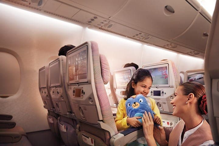 Female cabin crew giving a stuffed panda toy to smiling young girl in Emirates Economy Class