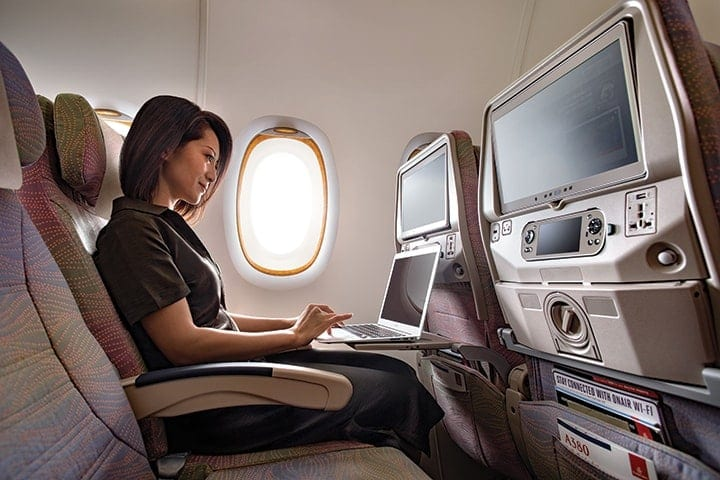 A woman working on her laptop in Emirates Economy Class on an Airbus A380