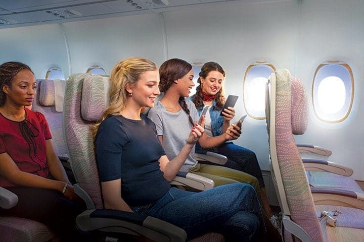 Three woman connecting to onboard Wi-Fi in Emirates Economy Class on an Emirates A380