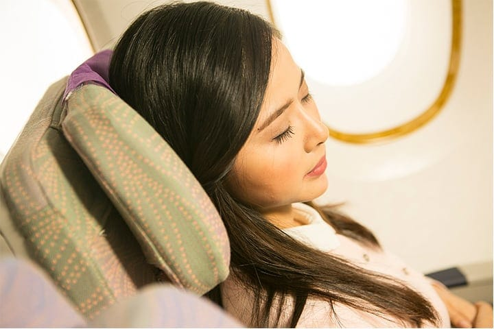 A woman is reclined in Emirates Economy Class on board an Emirates A380
