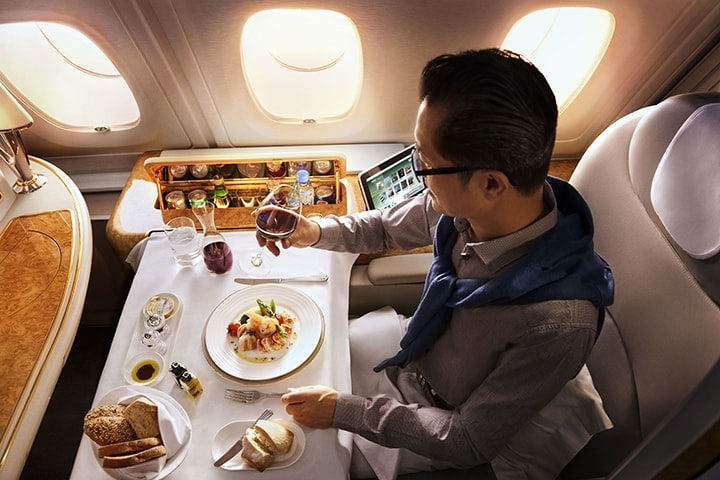 A man dines in Emirates First Class on an Emirates A380