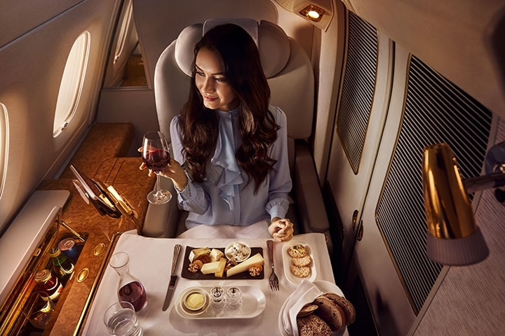 Een vrouw geniet van een kaasplankje en drankjes in Emirates First Class in een Emirates A380