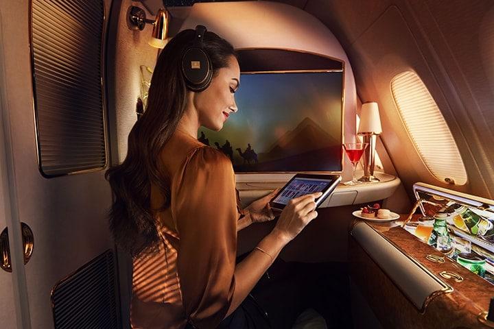 Een vrouw bekijkt de kanalen op het scherm van haar entertainment aan boord in Emirates First Class in een Emirates A380