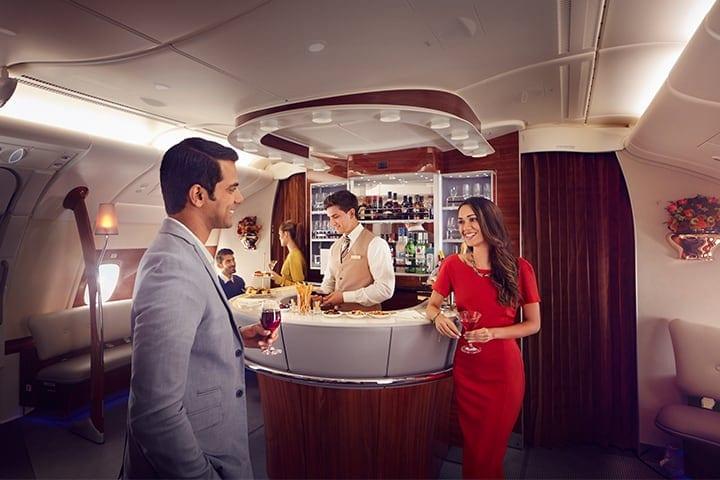Een man en vrouw genieten van een drankje en praten in de Emirates Onboard Lounge