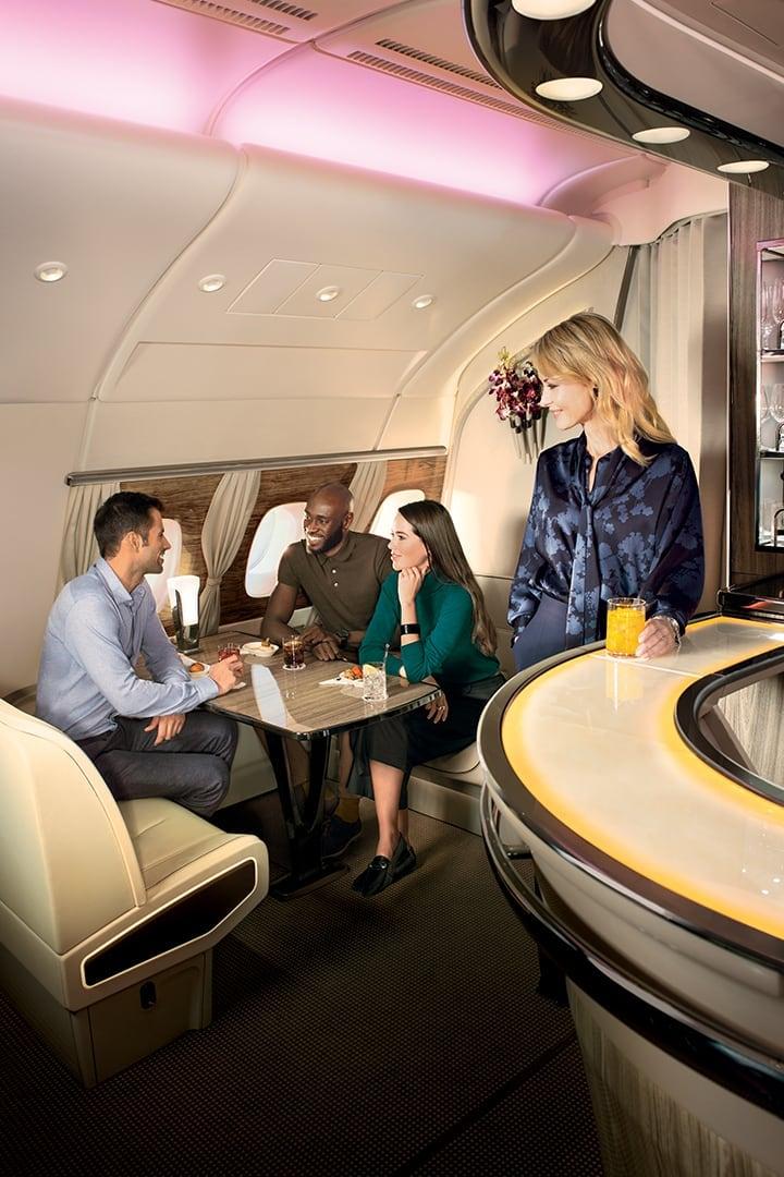 Bir kadın, bir grup insan Emirates A380 Uçak İçi Dinlenme Salonu'nda sosyalleşirken bardan bakıyor