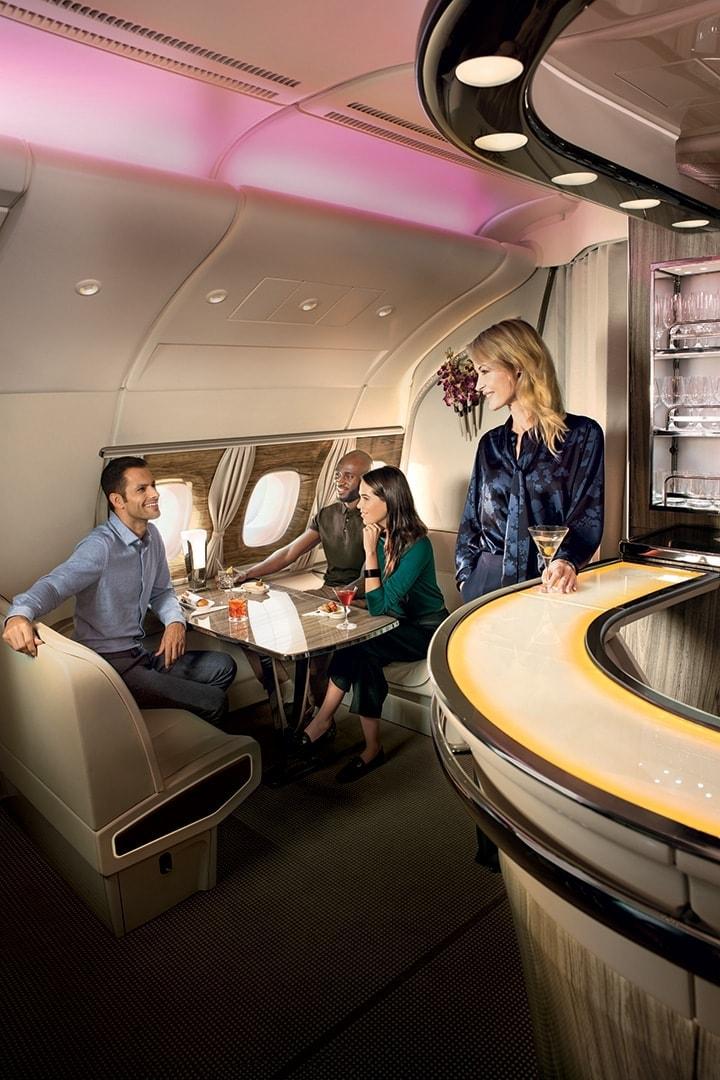 Een vrouw kijkt rond in een bar met een groep mensen die gezellig praten in de Emirates A380 Onboard Lounge