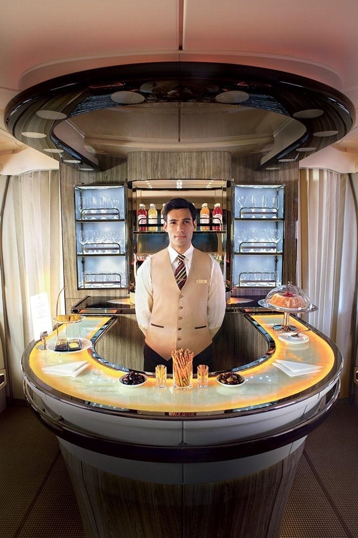 Bir Emirates kabin personeli Emirates A380 Uçak İçi Dinlenme Salonu'nda barın arkasında duruyor