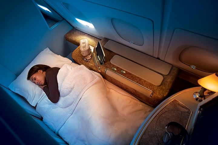 A woman sleeps on her fully flat bed in Emirates First Class on the Emirates A380