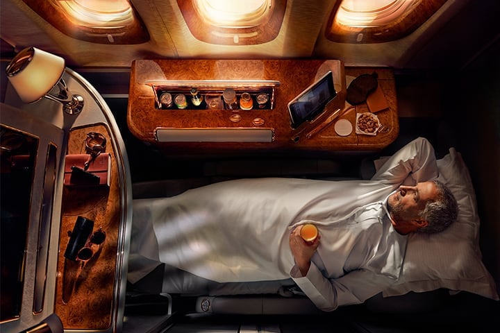 A man sleeps on his fully flat bed in Emirates First Class on the Emirates A380