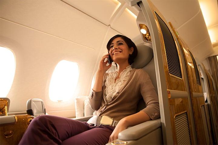 Bir kadın, Emirates A380 uçakta Emirates First Class'ta telefonuyla mobil dolaşım verisi kullanıyor