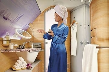 A woman uses hand cream after taking a shower on the Emirates A380