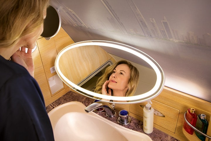 A woman applies moisturizer using the vanity mirror in the Emirates A380 Shower Spa