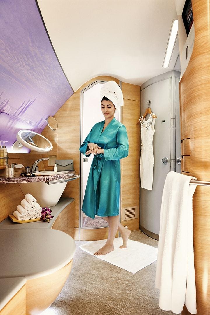 Een vrouw gebruikt douchespa-huidverzorgingsproducten in een Emirates A380