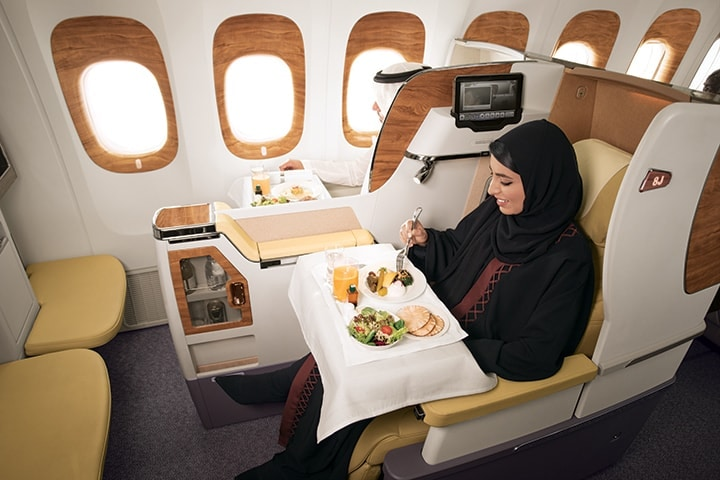 An Arab woman sitting in Business Class on a Boeing 777 enjoying her inflight meal