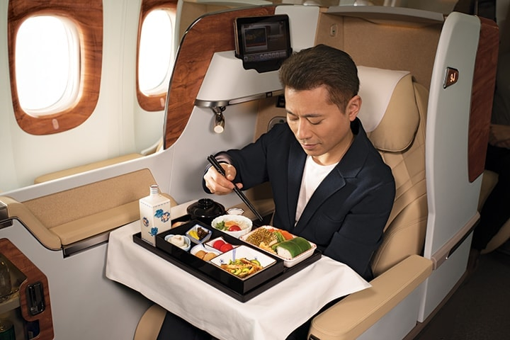 Japanese eating a traditional Japanese meal with chopsticks in Emirates Business Class on a Boeing 777