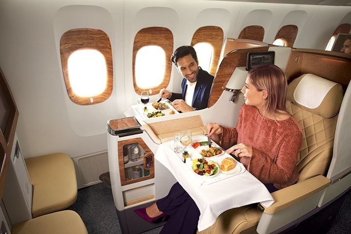 Couple sitting in Emirates Business Class on a Boeing 777 chatting and eating their onboard meals