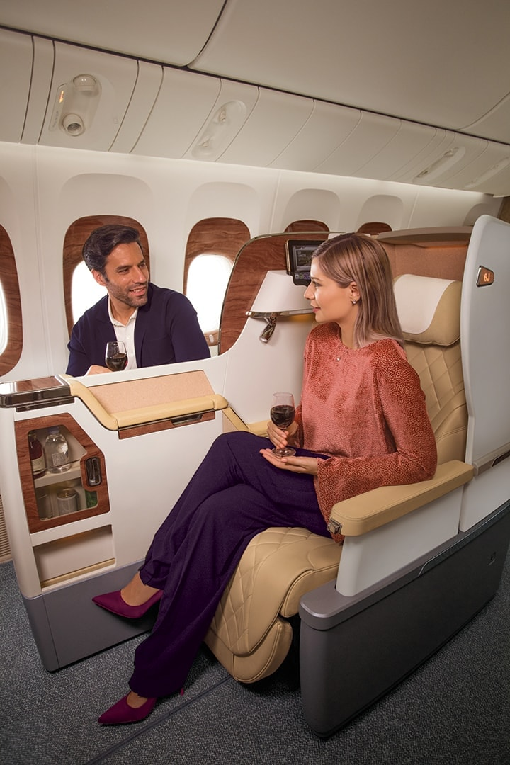 A couple chatting and enjoying a glass of wine while sitting in their seats in Emirates Business Class on a Boeing 777