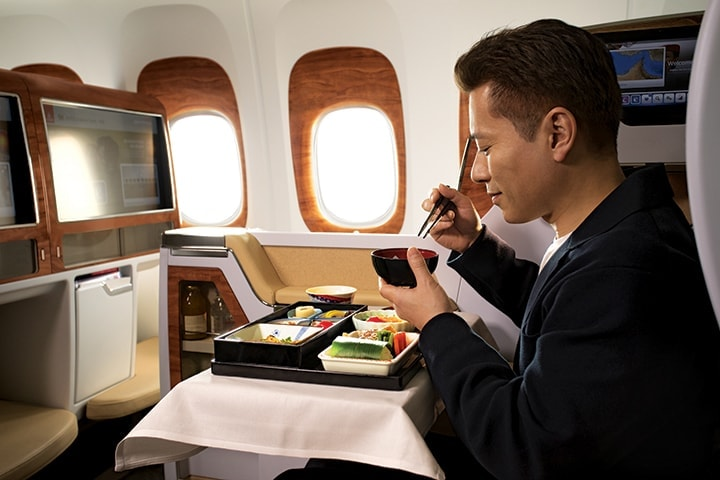 Japanese man enjoying a traditional Japanese meal in Emirates Business Class on a Boeing 777
